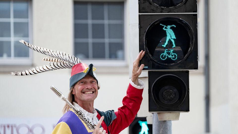 Ein Stadtführer im Rattenfänger-Outfit an der Rattenfänger-Ampel in Hameln