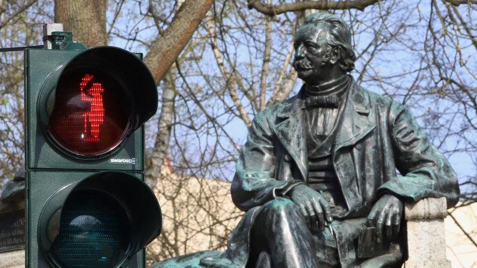 Eine Ampelanlage zeigt Theodor Fontana neben einem Denkmal des Dichters
