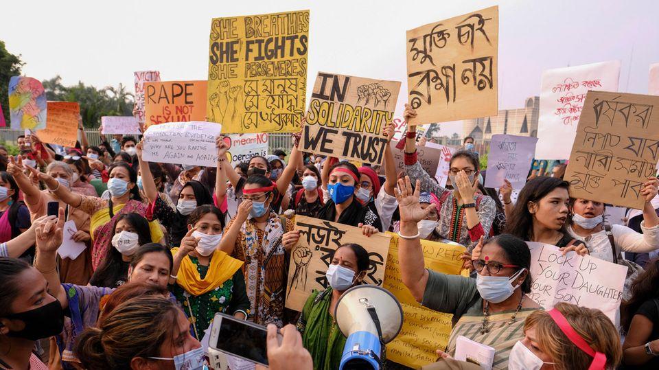 Frauen demonstrieren auf der Straße und halten Schilder hoch