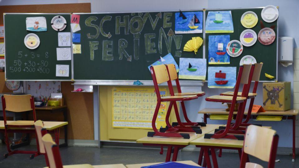 """Leeres Klassenzimmer, Stühle sind hochgestellt, an der Tafel steht """"Schöne Ferien""""."""