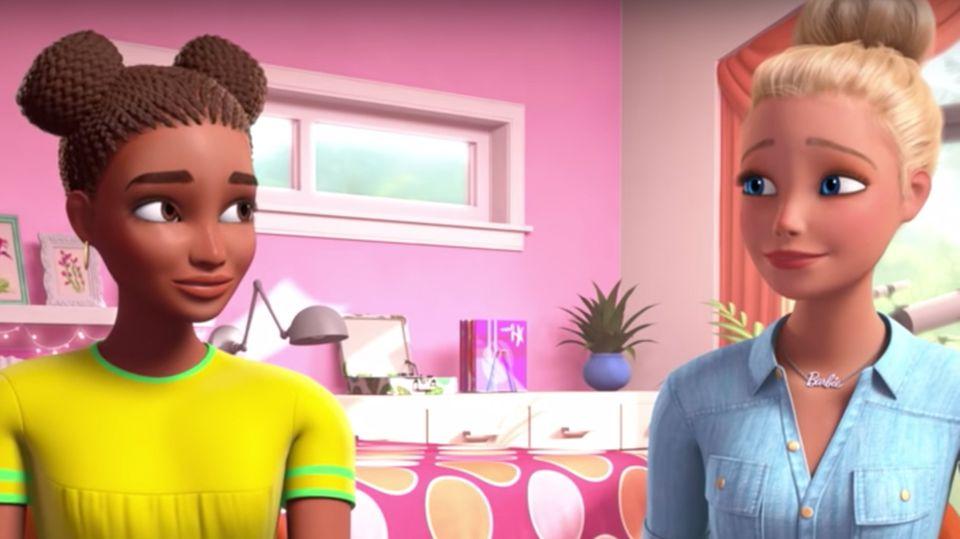 Links sitzt eine schwarze junge Frau in einem gelben T-Shirt am Tisch, rechts neben ihr die weiße und blonde Barbie