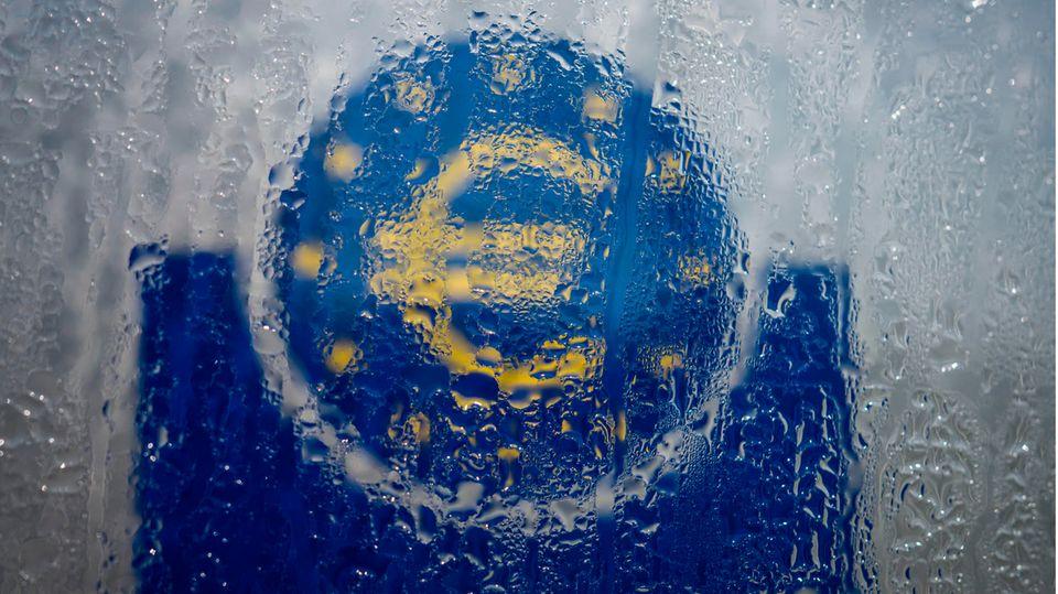 Wasser hat sich an einem gläsernen Schild mit Euro-Symbol niedergelassen