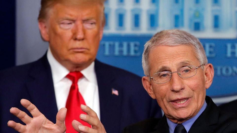 Während Anthony Fauci - mit Brille und weißem Seitenscheitel - am Rednerpult gestikuliert, steht Trump mürrisch schräg dahinter