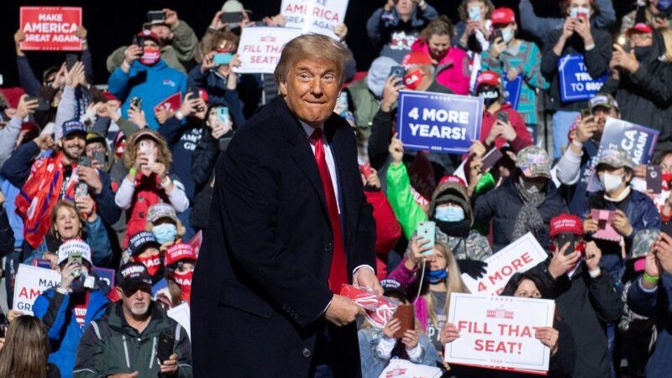 Trump wirft Maske bei Wahlkampfveranstaltung weg, im Hintergrund viele Anhänger ohne Maske zu sehen.