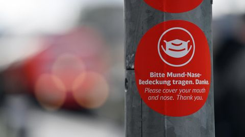 """""""Bitte Mund-Nase-Bedeckung tragen"""" steht in deutscher und englischer Sprache auf einem Aufkleber"""