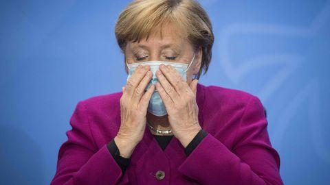 Angela Merkel legt eine Maske an und sieht erschöpft aus