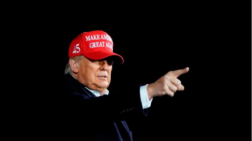 Präsident Trump trägt rote MAGA Cap und deutet mit dem Zeigefinger.
