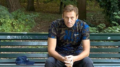 Kreml-Kritiker Alexej Nawalny sitzt auf einer Bank im Wald und schaut in die Kamera