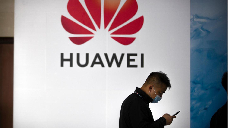 Ein Mann geht an einer Huawei-Werbetafel auf einer Expo vorbei