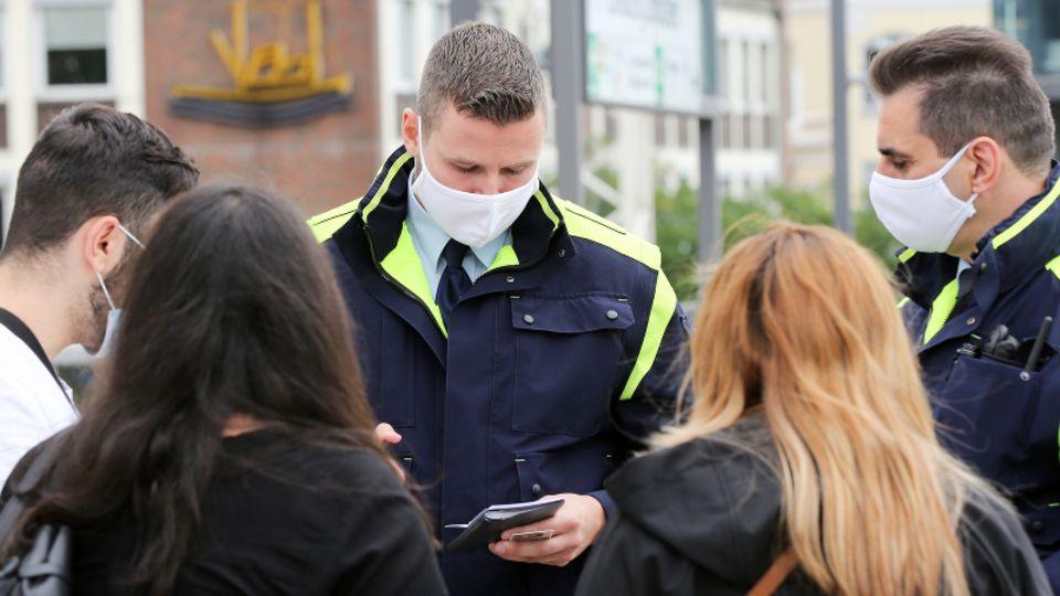 Beamte kontrollieren in Hamburg die Maskenpflicht und stellen Strafe aus.