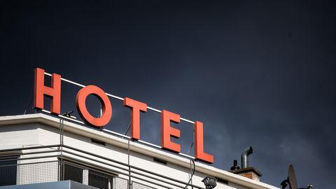 Rote HOTEL-Buchstaben auf Hoteldach, im Hintergrund dunkle Wolken