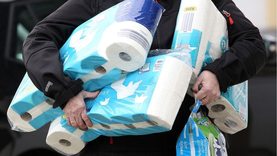 Ein Mann hat den ganzen Arm voller Packungen Toilettenpapier