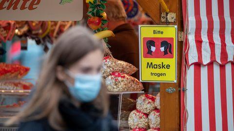 """Ein Schild mit der Aufschrift """"Bitte Maske tragen"""", im Vordergrund eine junge Frau"""