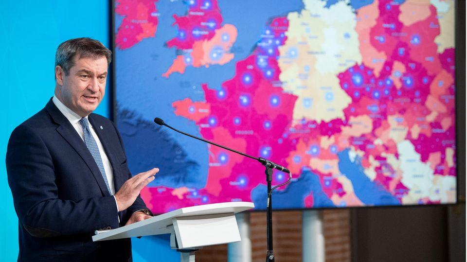 Markus Söder spricht auf einer Pressekonferenz vor einem Monitor mit Corona-Daten