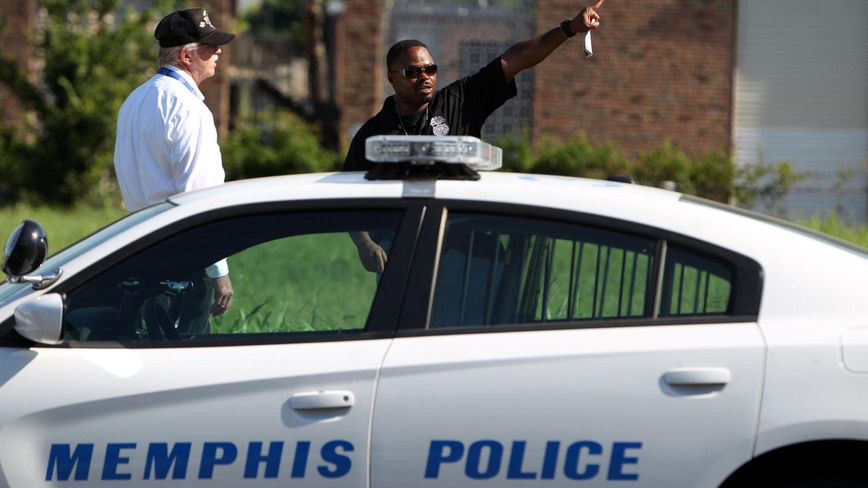"""Zwei Männer stehen hinter einem Auto mit der Aufschrift """"Memphis Police"""""""