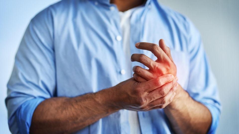 Der Mann hat Schmerzen in der Hand