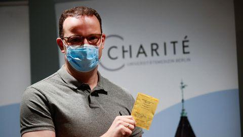 Jens Spahn hält seinen Impfausweis in die Kamera.