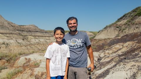 Der zwölfjährige Nathan und sein Vater Dion blicken lächelnd in die Kamera.