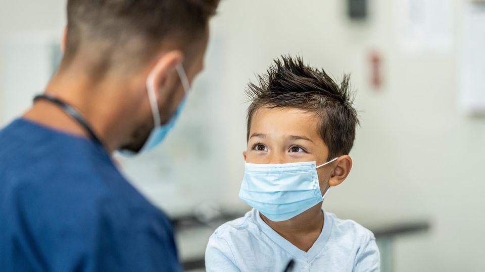 Junge mit Maske in Arztpraxis