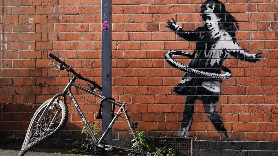 Kunstwerk von Banksy in Nottingham: Ein Mädchen spielt mit Hulla-Hoop-Reifen, davor liegt ein kaputtes Fahrrad