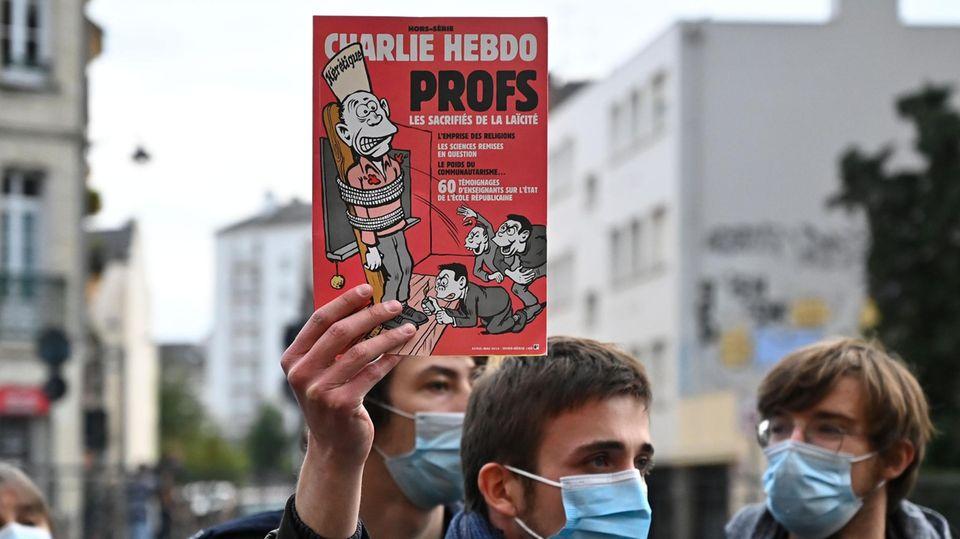 """Ein Mann hält während einer Demonstration in Rennes ein """"Charlie Hebdo""""-Cover in der Hand"""