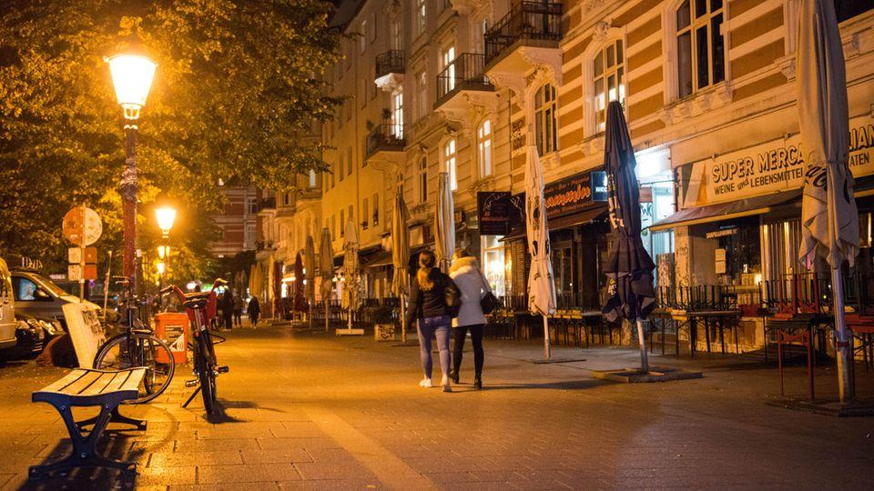 Hochgestellte Bänke stehen auf Tischen im Hamburger Schanzenviertel, in dem nur noch wenige Menschen unterwegs sind