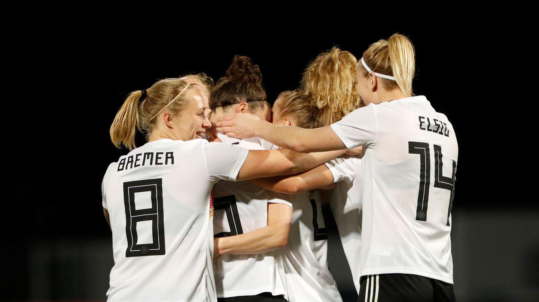 Fußballerinnen in weißen Trikots mit schwarzem Flock und in schwarzen Hosen bilden eine Jubeltraube