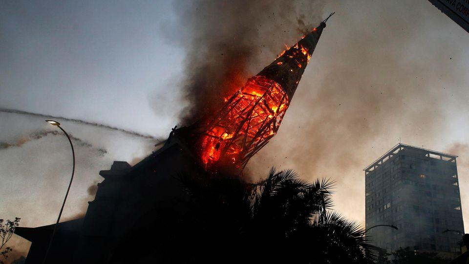 """Santiago de Chile, Chile. Am Jahrestag der heftigen Proteste gegen soziale Ungleichheit und die konservative Regierung in Chile sind in der Hauptstadt Santiago de Chile mindestens zweiGotteshäuserin Brand gesteckt worden. Hier stürzt der Turm der Kirche """"Parroquía de la Asunción"""" einstürzte, weil die Struktur des Gebäudes den Flammen nicht mehr standhielt. Sie ist eine der ältestenKirchenSantiagos. Chilenischen Medienberichten zufolge war zuvor auch die """"Iglesia de San Francisco de Borja"""" angezündet worden, die regelmäßig von der Polizei für Zeremonien genutzt wird."""