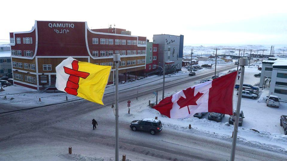Eine kanadische Flagge und die Flagge Nunavuts wehen in Iqaluit,der Hauptstadt des kanadischen Territoriums Nunavut