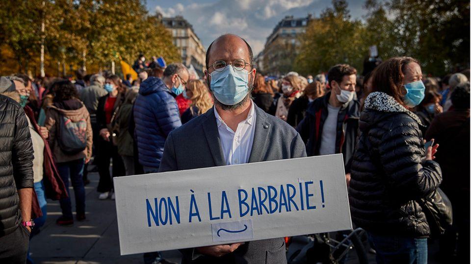 """Ein Mann steht mit einem Pappschild """"Non à la barbarie"""" auf einer Demo in Paris"""