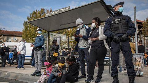 """Am Dach eines Bushaltestellen-Häuschens steht """"College Bois d'Aulne"""". Vor dem Häuschen warten Schüler und ein Polizist"""