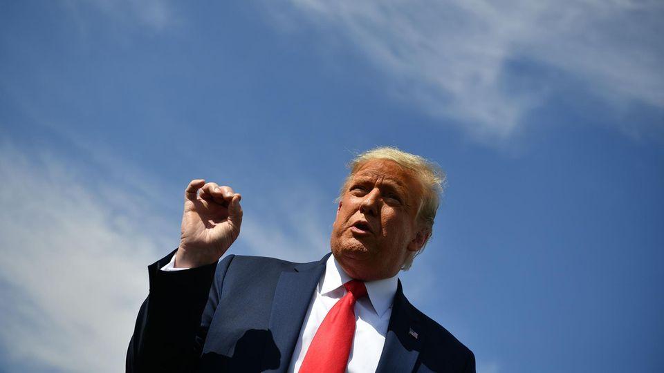 Unter einem blauen Himmel steht US-Präsident Trump an einem Rednerpult und gestikuliert mit der rechten Hand