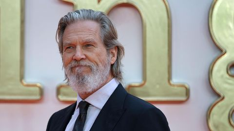 Jeff Bridges, ein Mann mit zurückgekämmten, schulterlangen, grauen Haaren steht im Anzug auf einem roten Teppich