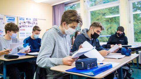 Schüler einer 13.Klasse sitzenmit Mund-Nasen-Bedeckungen im Deutsch-Unterricht