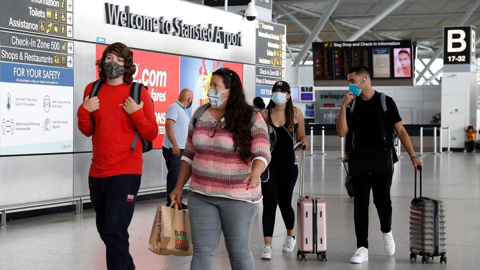 """Vier junge Erwachsene rollen ihre Koffer unter einem Schild """"Welcome to Stansted Airport"""" durch ein Flughafen-Terminal"""