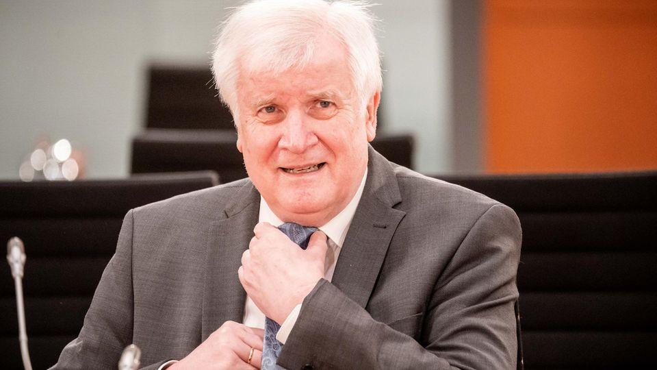 Bundesinnenminister Horst Seehofer richtet mit beiden Händen seine blaue Krawatte