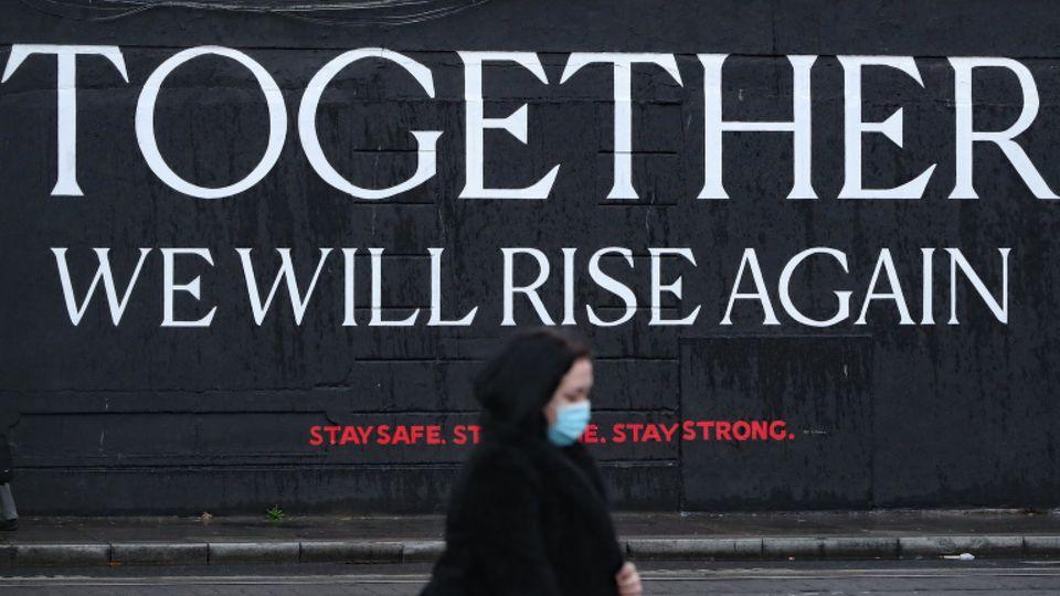 Eine Frau geht an einem Wandbild im Stadtzentrum von Dublin vorbei, das den Bürgern in der Corona-Zeit Mut machen soll.