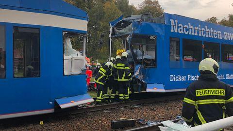 Einsatzkräfte der Feuerwehr arbeiten nach einer Straßenbahnkollision am Unfallort.