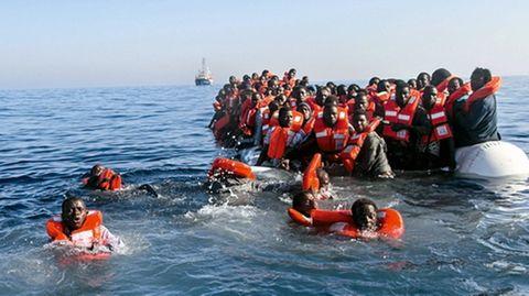 Flüchtlinge schwimmen im Wasser vor einem sinkenden Schlauchboot