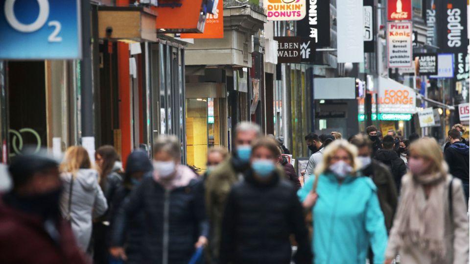 Eine gut besuchten Einkaufsstraße in Köln, viele Menschen tragen eine Maske.