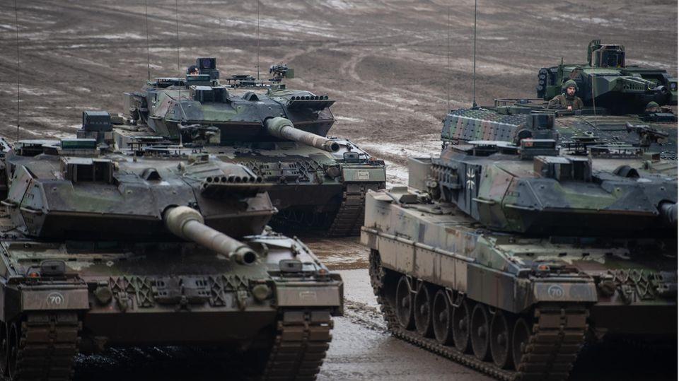 Drei Kampfpanzer der Bundeswehr vom Typ Leopard 2A6 und ein Schützenpanzer vom Typ Puma stehen bei einer Übung im Gelände