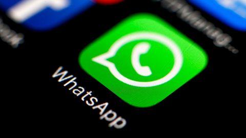 Auf einem Smartphone-Display leuchtet das grüne Logo von WhatsApp