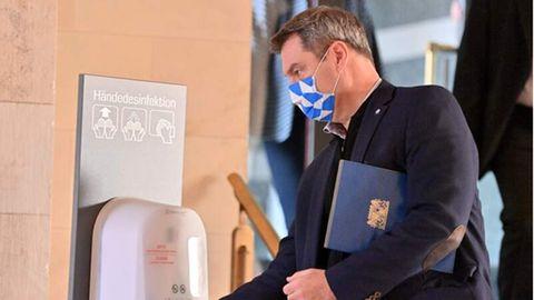 Der bayrische Ministerpräsident Markus Söder desinfiziert sich die Hände.