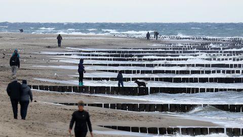 Graal-Müritz in Mecklenburg-Vorpommern:Spaziergänger sind am Strand unterwegs, die Strandkörbe sind alle im Winterquartier.