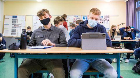 Schüler sitzen in der Klasse mit Schutzmasken