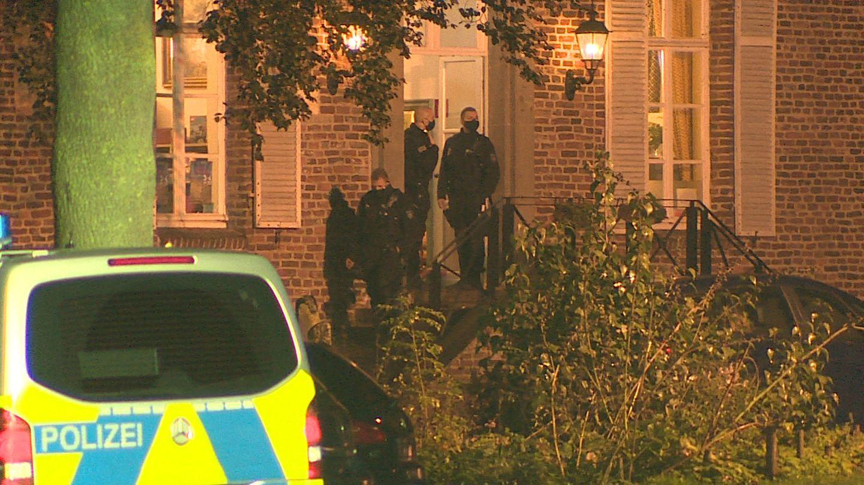 Polizeibeamte gehen in ein Haus auf dem Areal einer Eventagentur in Goch am Niederrhein