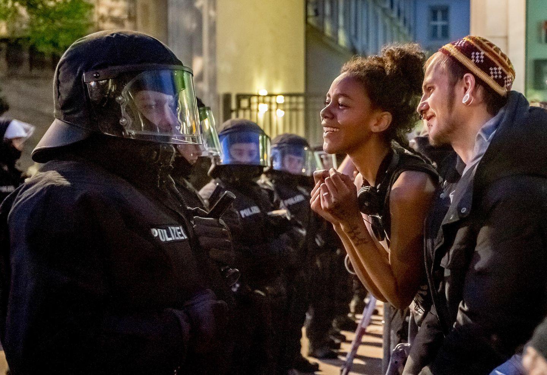 """Die jährliche, fast schon ritualisierte Demonstration zum 1. Mai in Berlin, hier 2013. Dies war mein erstes Foto für die Deutschland-Serie. Ich war den ganzen Weg des Protestzugs von Kreuzberg bis """"Unter den Linden""""mitgelaufen. Erst als die Teilnehmer, kurz vor dem Hotel Adlon, von Polizisten in Darth-Vader-Ausrüstung gestoppt und kurzzeitig eingekesselt wurden, entstand dieses Bild, das mich an eine Foto-Ikone von Marc Riboud erinnert: ein Mädchen mit Blume in der Hand vor Bajonetten; beim Peace Marchin Washington D.C. 1967."""