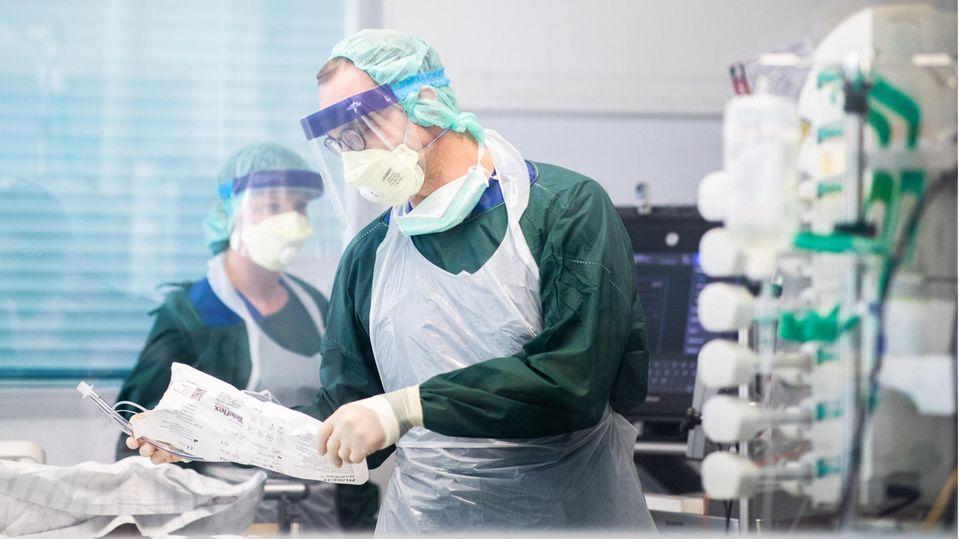 Krankenpfleger auf einer Intensivstation mit einem Covid-19-Patienten