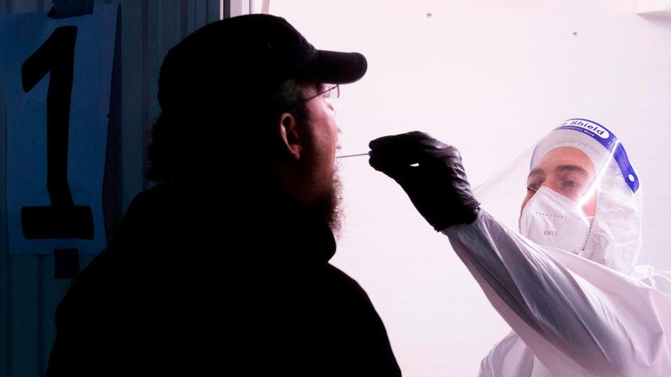 Ein Helfer der Johanniter nimmt im Corona Testzentrum am Flughafen Hannover einen Abstrich