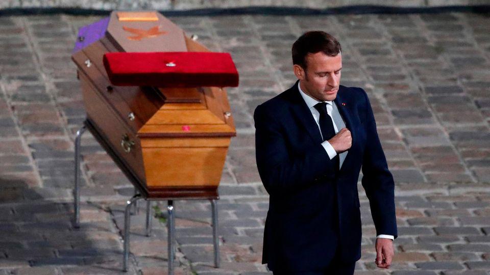 Im schwarzen Anzug geht Emmanuel Macron über einen gepflasterten Hof. Hinter ihm steht ein hellbrauner Sarg mit Orden darauf